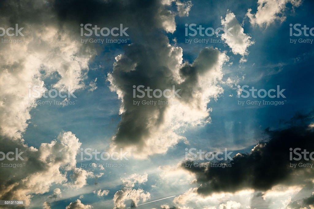 sun rays breaking through the clouds on dark blue sky stock photo