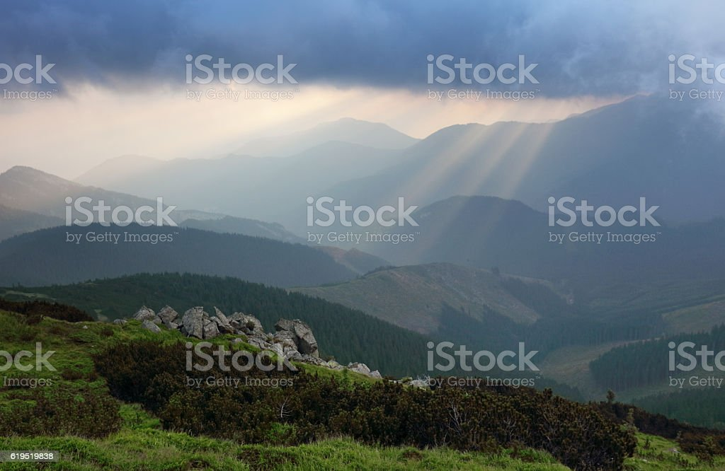 sun rays bursting through the skies in late afternoon stock photo