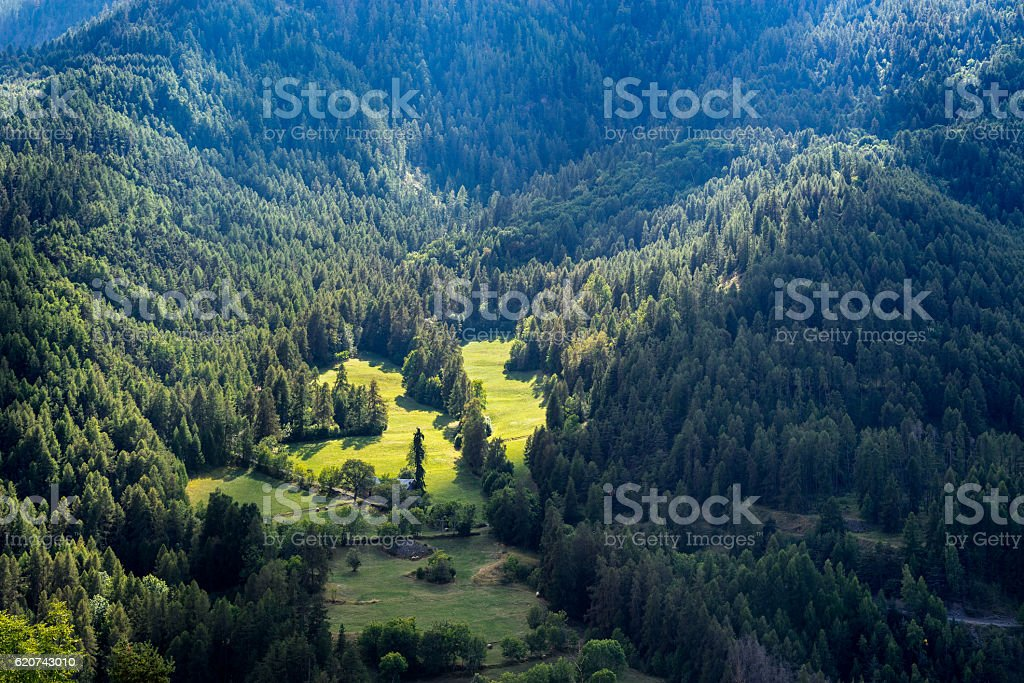 Sun rays on a farm and mountain slopes, Alps, France stock photo