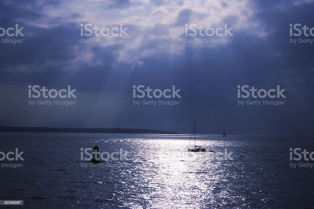 Sun rays over ocean stock photo