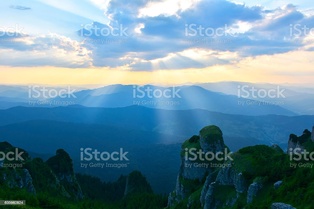 Sun rays seen in early morning over the mountains stock photo