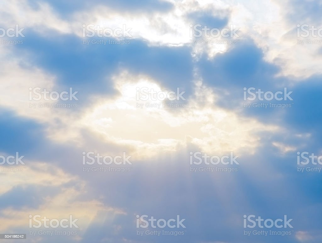 sun rays shine through the clouds stock photo