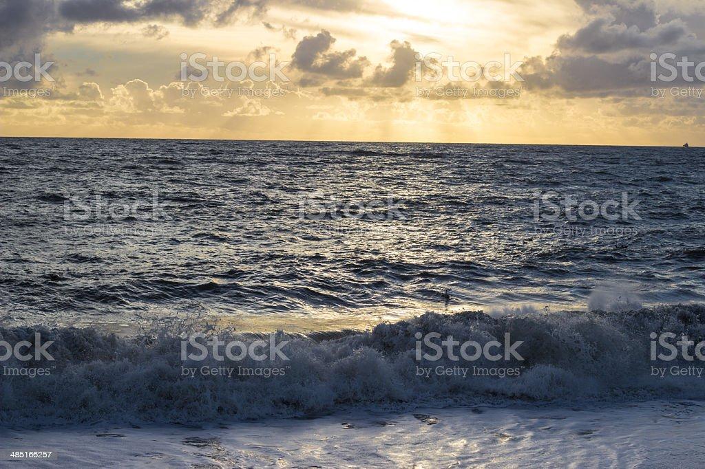 Sun rays through cloud on Hove beach stock photo