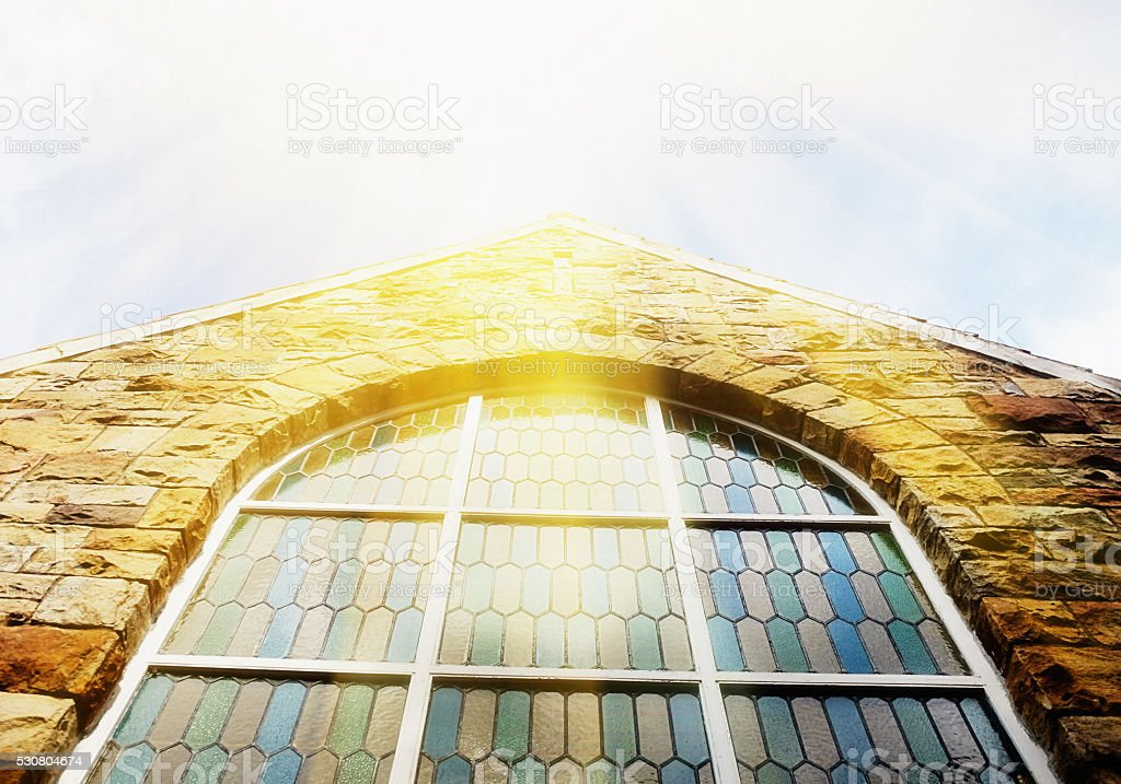 Sun reflecting off stained-glass church window stock photo