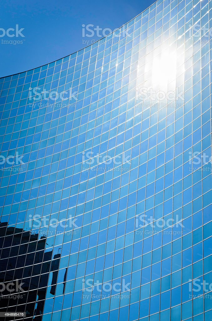 Sun reflecting on a curved steel and glass office building royalty-free stock photo