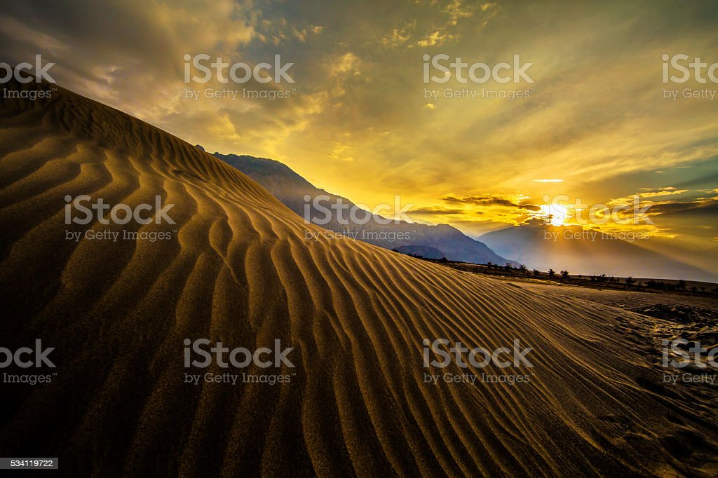 Sun rise at sand dunes against. stock photo