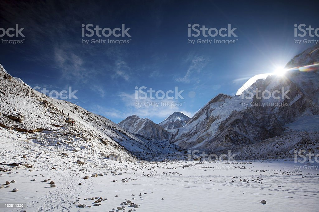 Sun rising behind the high altitude mountains stock photo