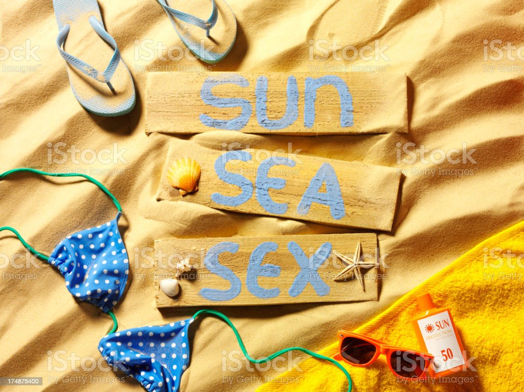Sun, Sea and Sex on a Sign in the Sand royalty-free stock photo