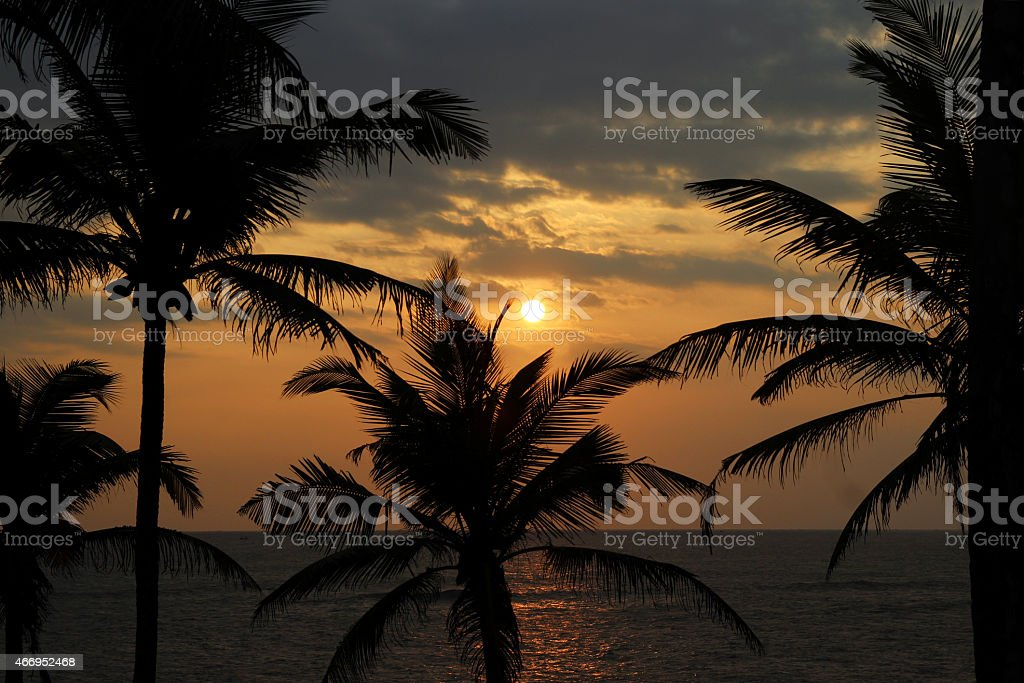 sun sets over the horizon on tropical beach royalty-free stock photo