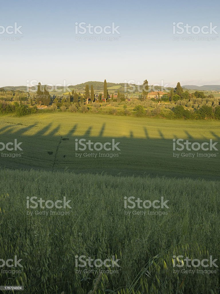 Sun sets over Tuscan farmland with farm in the distance royalty-free stock photo