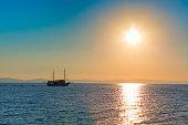 Sun setting at the sea with sailing ship