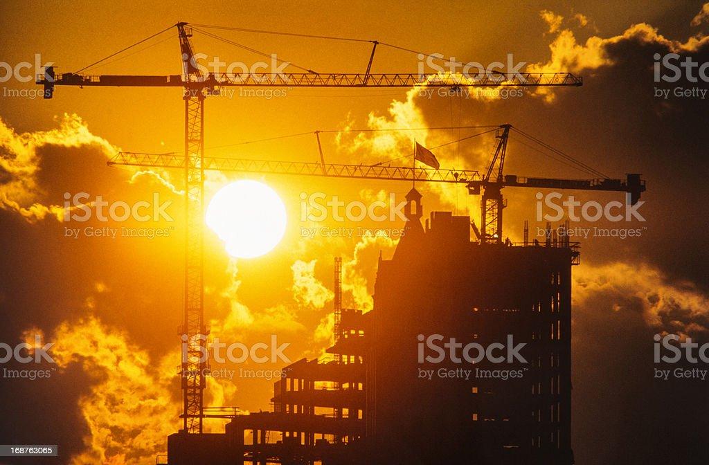 Sun Setting Behind Construction Cranes stock photo
