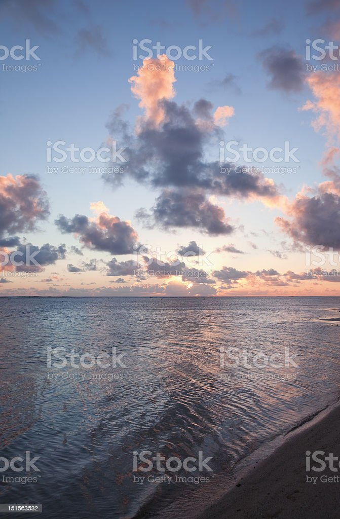 Sun setting behind Cumulus Clouds over Ocean and Island royalty-free stock photo