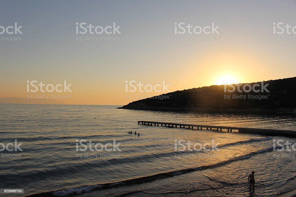 Sun setting behind sloping mountain stock photo