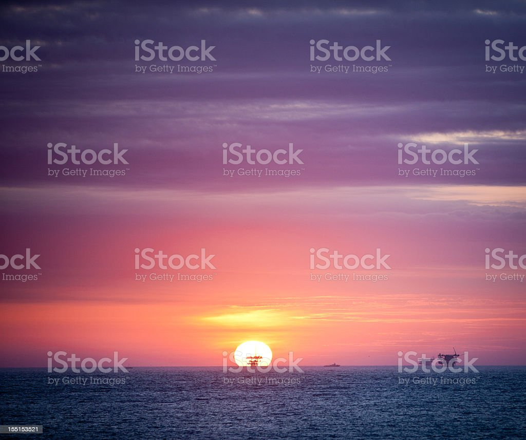 Sun setting directly behind oil platform in the Pacific Ocean royalty-free stock photo