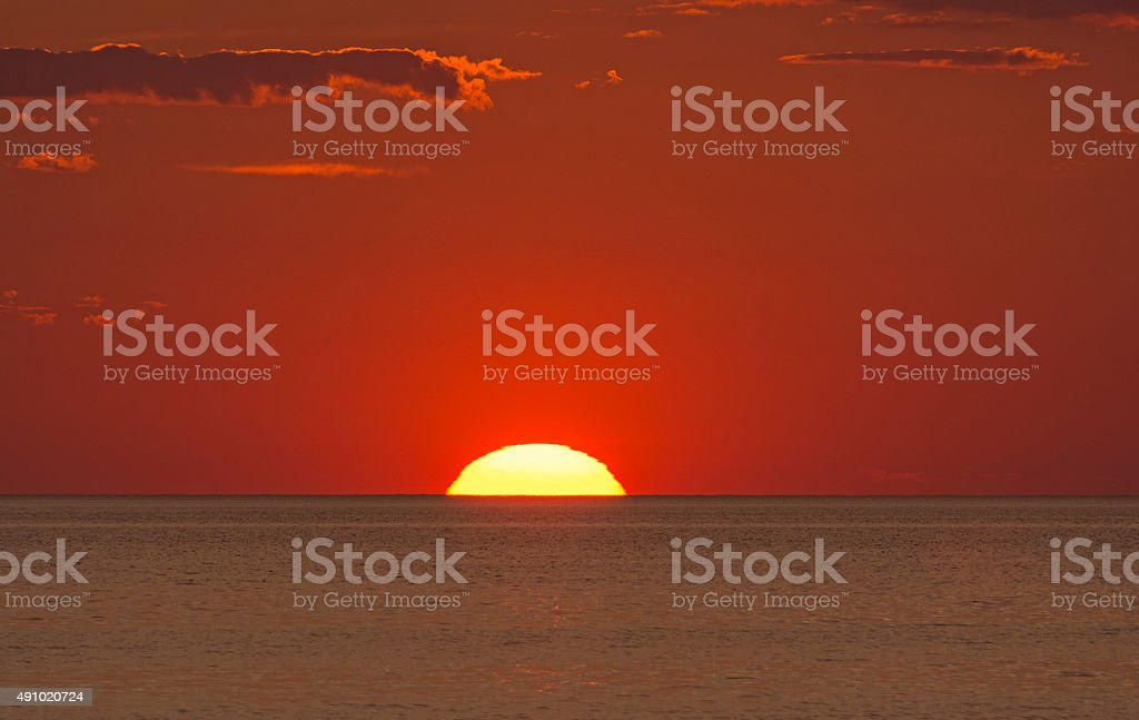 Sun Setting into the Ocean stock photo