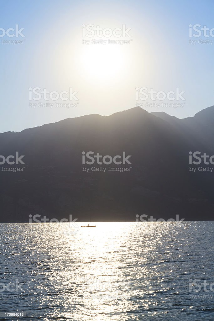 sun setting over lake with little boat backlit royalty-free stock photo