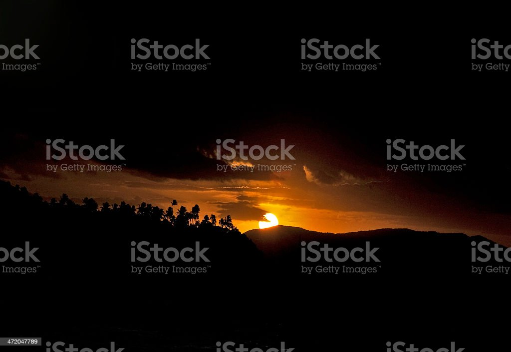 Sun setting with silhouette stock photo