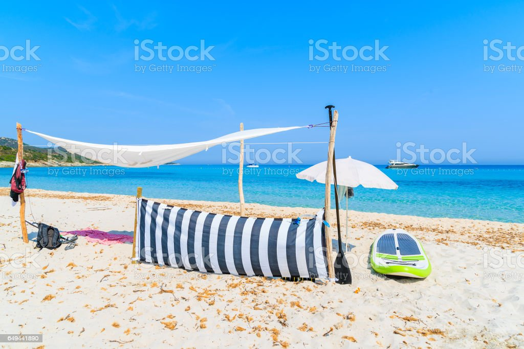Sun shade and surfboard on white sand Saleccia beach, Corsica island, France stock photo