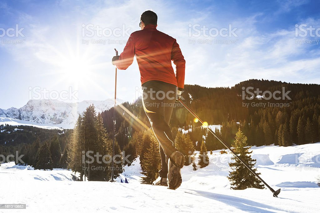 Sun shines on a man cross country skiing in mountains. stock photo