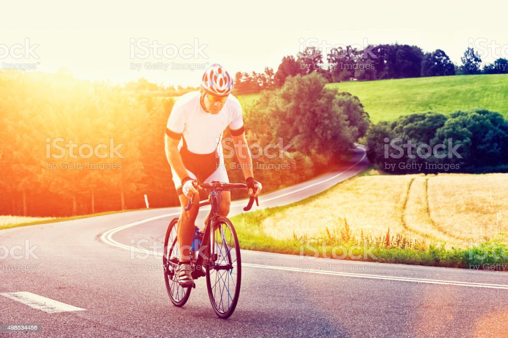 Sun shines on athlete who rides his bicycle up hill stock photo