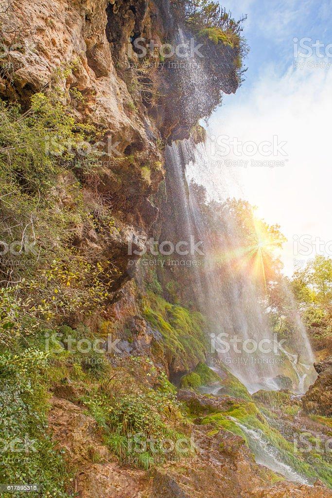 sun shines through waterfall stock photo