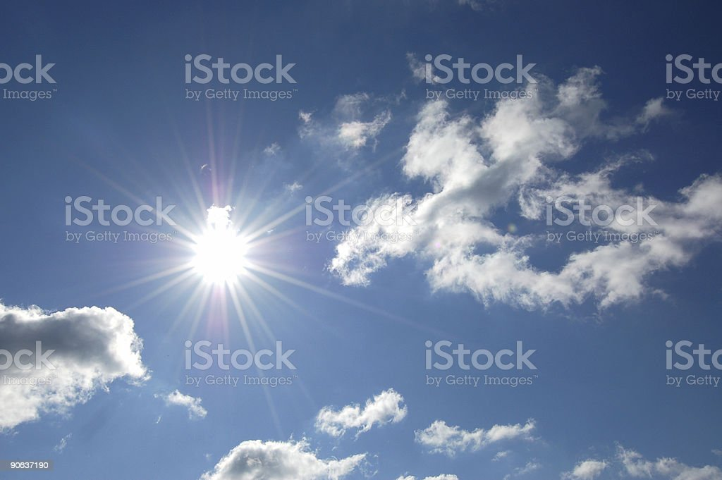 Sun shining bright on blue sky with scattered clouds royalty-free stock photo