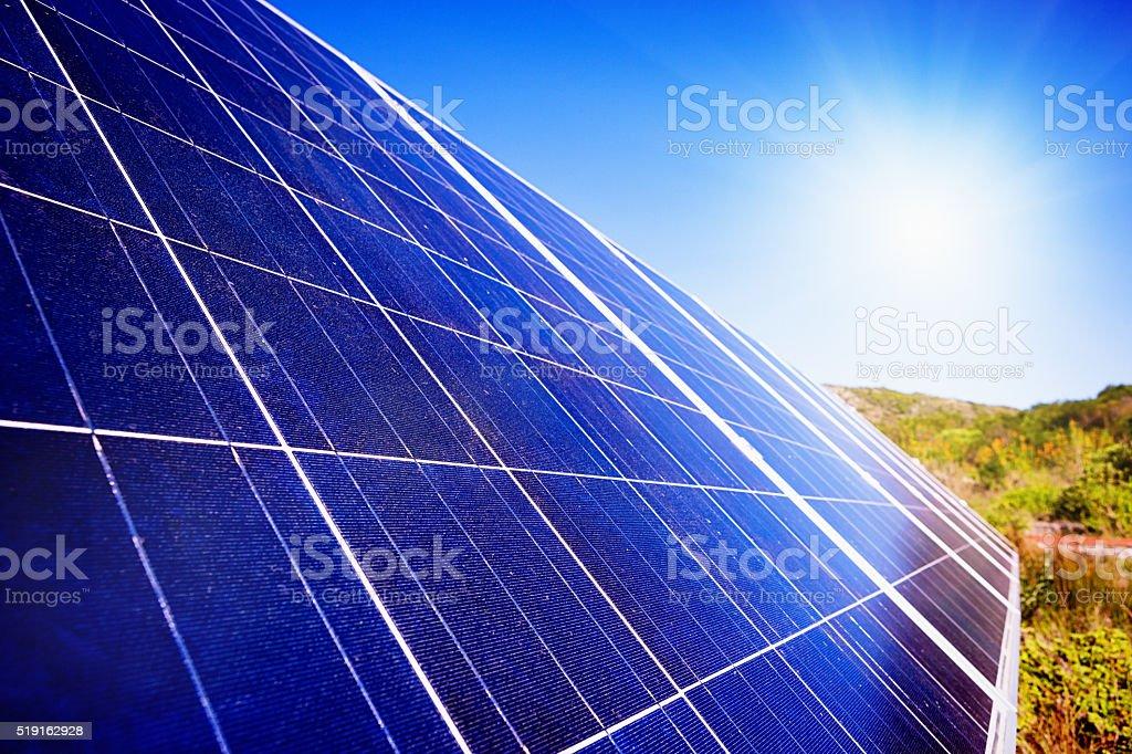 Sun shining brightly on solar power panel array stock photo