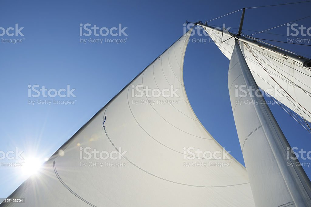 Sun shining from behind the sails of a yacht stock photo