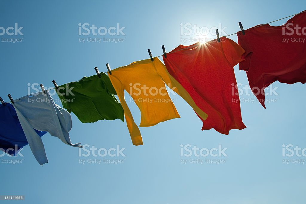 Sun shining over a laundry line with bright clothes stock photo