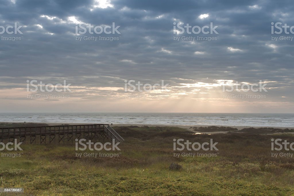 Sun Shining through Clouds on Beach royalty-free stock photo