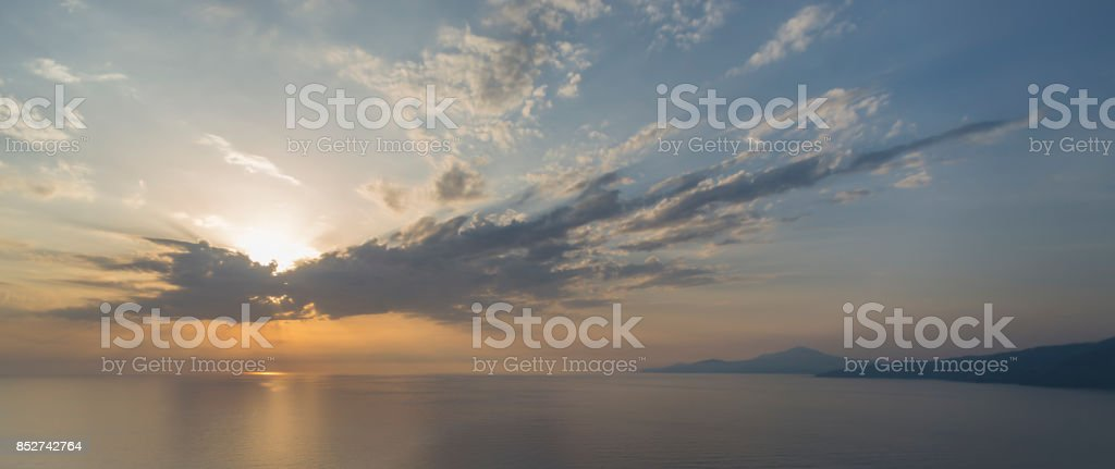 Sun shining through clouds over the mediterranean Sea and the coastline at Palinuro cape in the Cilento region in southern Italy stock photo
