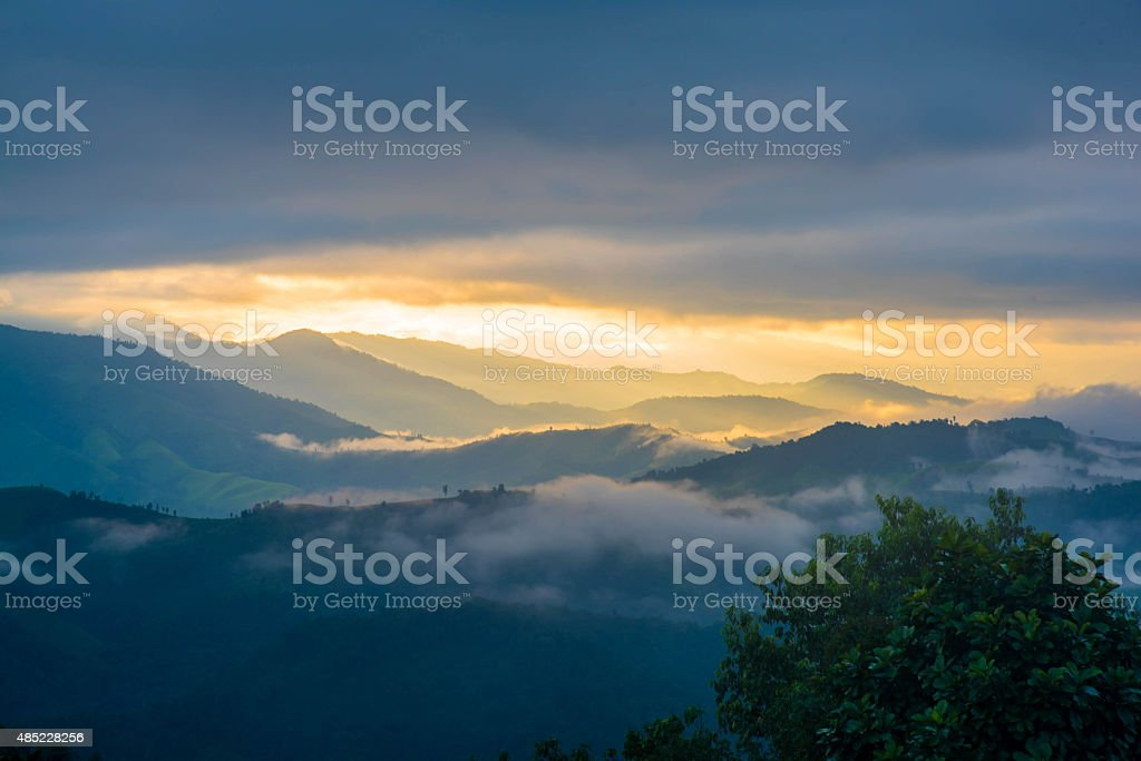 Sun shining through the clouds with silhouetted mountians stock photo