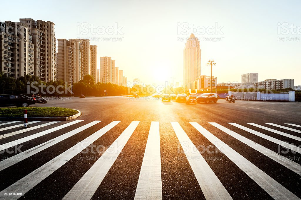 sun skyline and traffic on urban road through city buildings stock photo