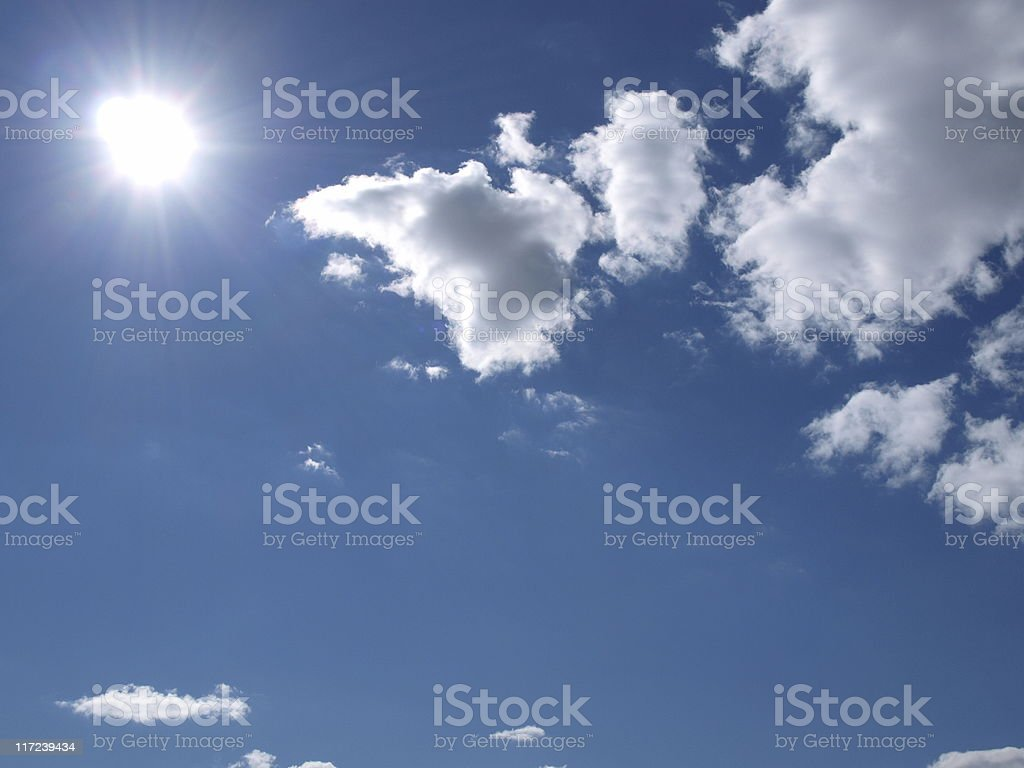 Sun sparkles in blue sky with clouds stock photo