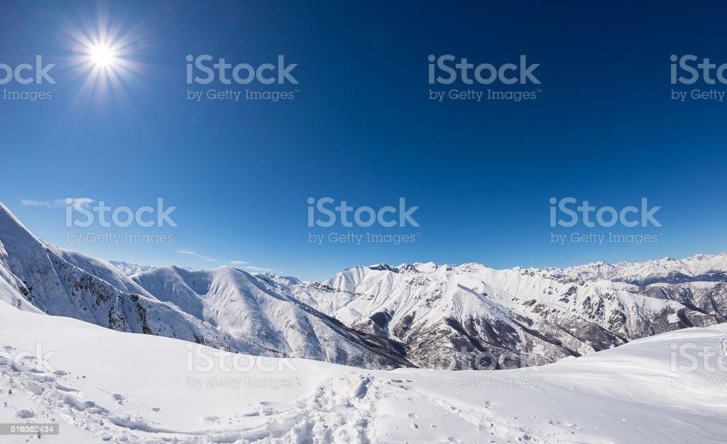 Sun star glowing over snowcapped mountain range, italian Alps stock photo