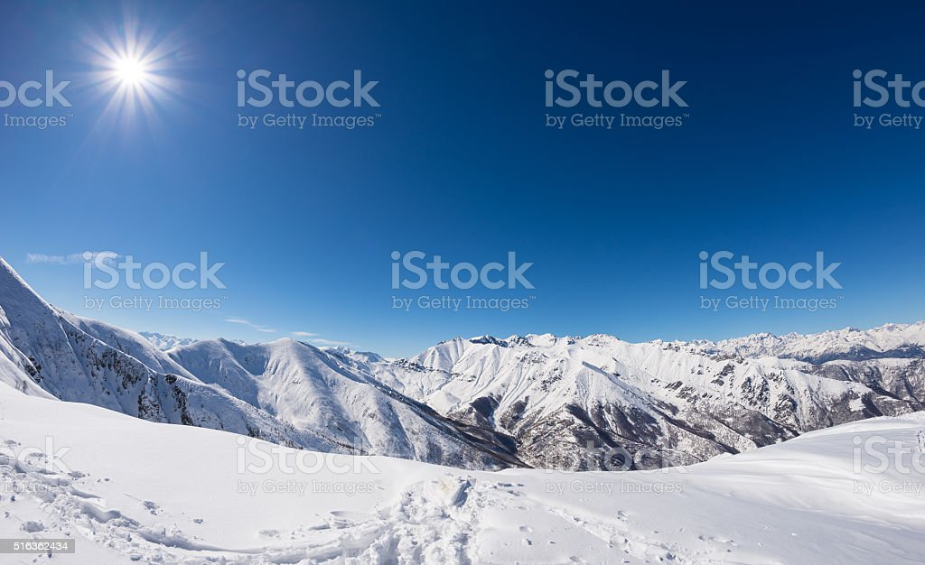 Sun star glowing over snowcapped mountain range, italian Alps stock photo
