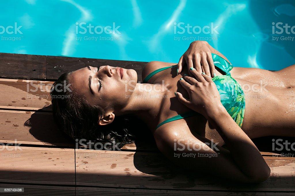 sunbath by pool stock photo