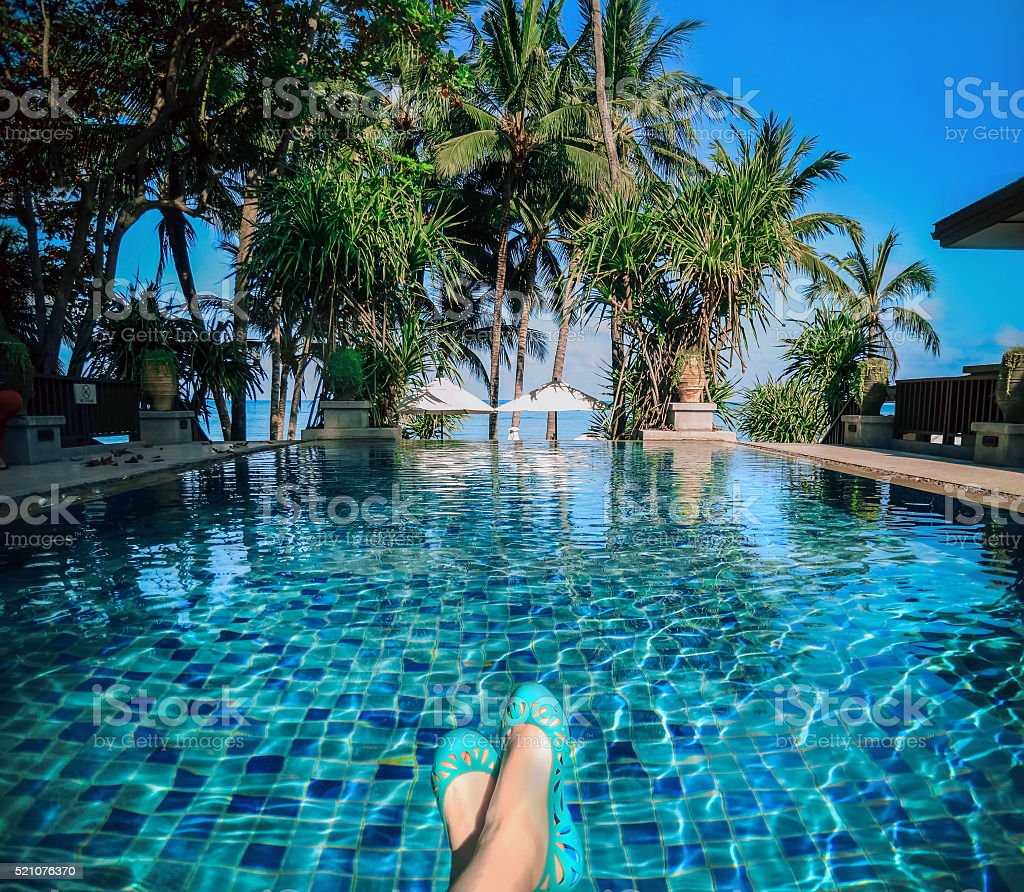 Sunbathing by the hotel tourist resort swimming pool stock photo