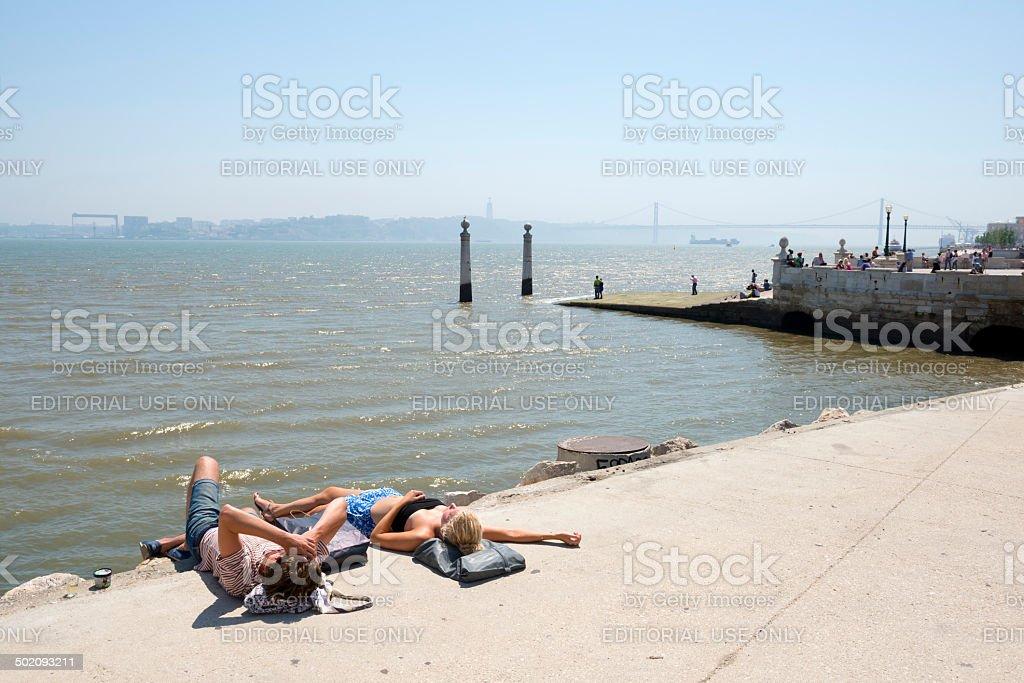 Sunbathing couple at Cais das Colunas in Lisbon, Portugal stock photo