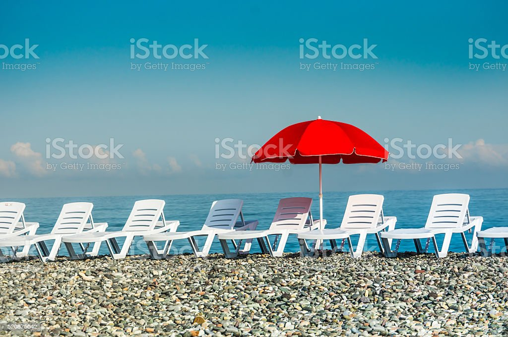 Sunbathing plastic beds and red umbrella on the beach stock photo