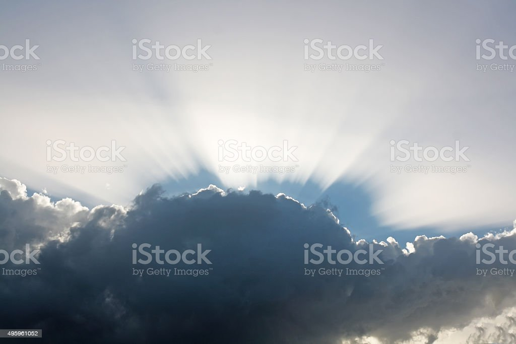Sunbeam behind clouds stock photo