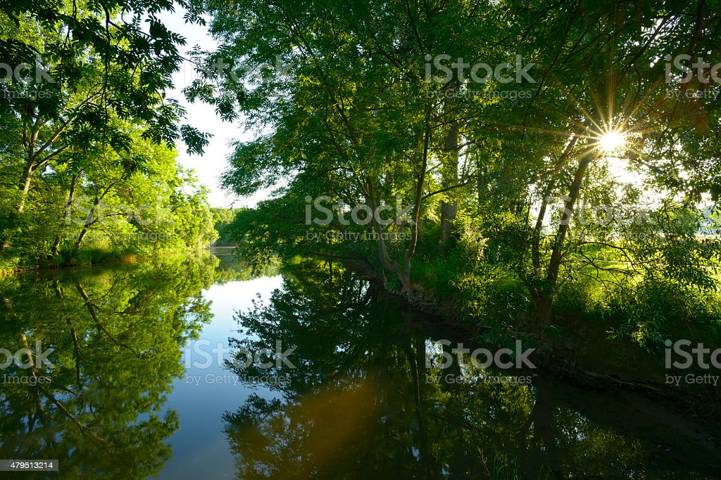 Sunbeam on a Small River at Sunrise stock photo