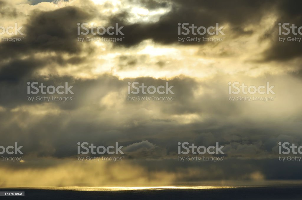 Sunbeams in cloudy sky above the sea royalty-free stock photo