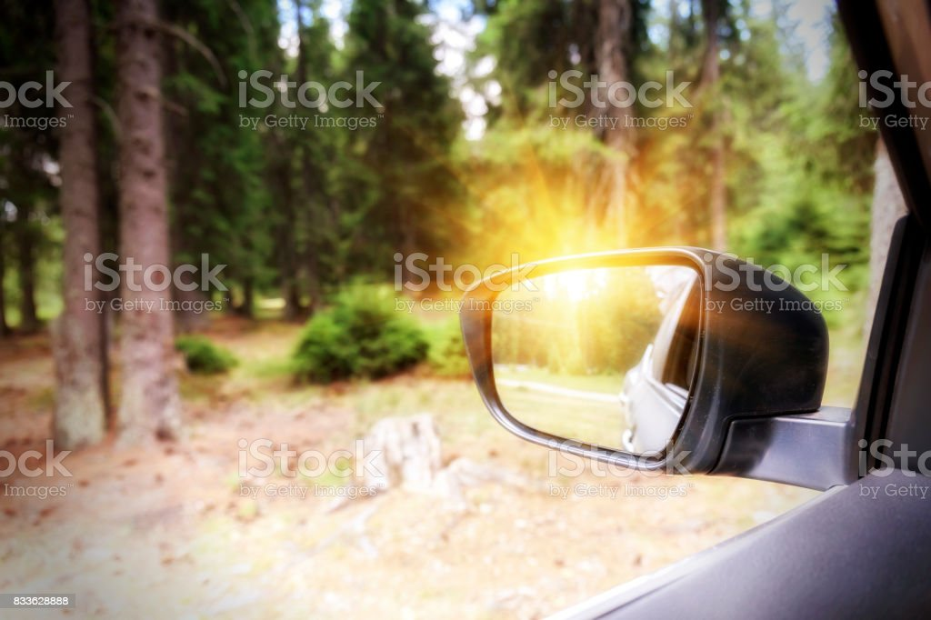 Sunbeams in the side mirror of car in the Apuseni mountains of Transylvania stock photo