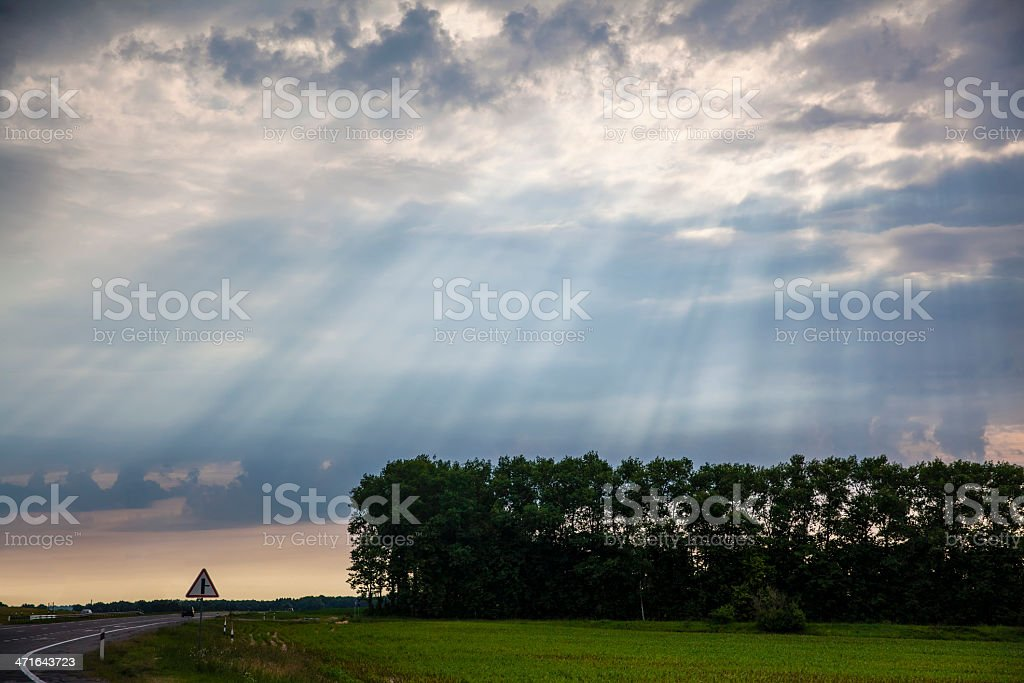 Sunbeams over highway and forest royalty-free stock photo