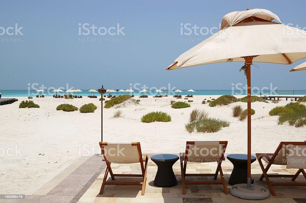 Sunbeds and umbrellas at beach of luxury hotel, Abu Dhabi stock photo