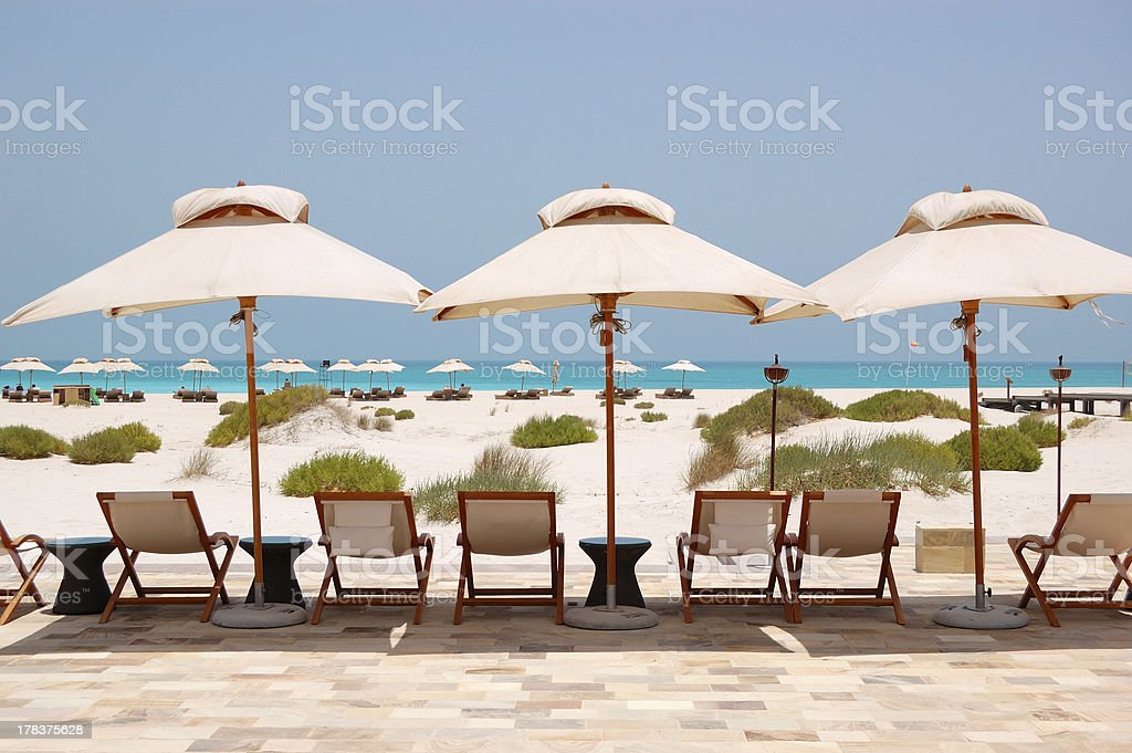 Sunbeds and umbrellas at the beach of luxury hotel stock photo