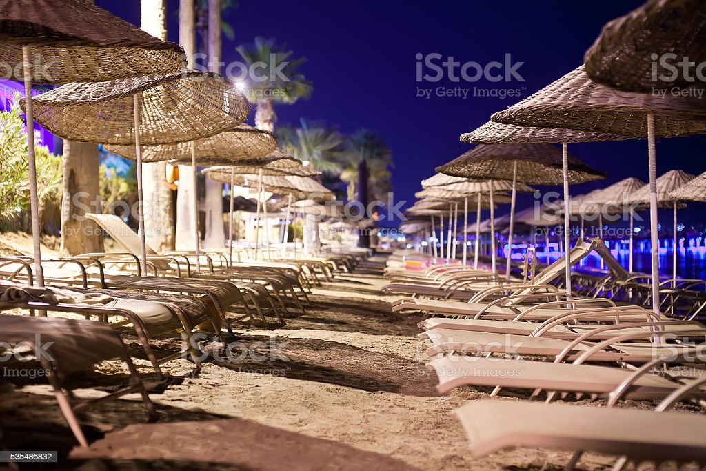 Sunbeds and umbrellas on the beach in the evening stock photo