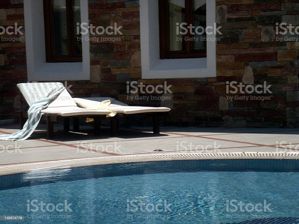 Sunbeds by the swimming pool royalty-free stock photo